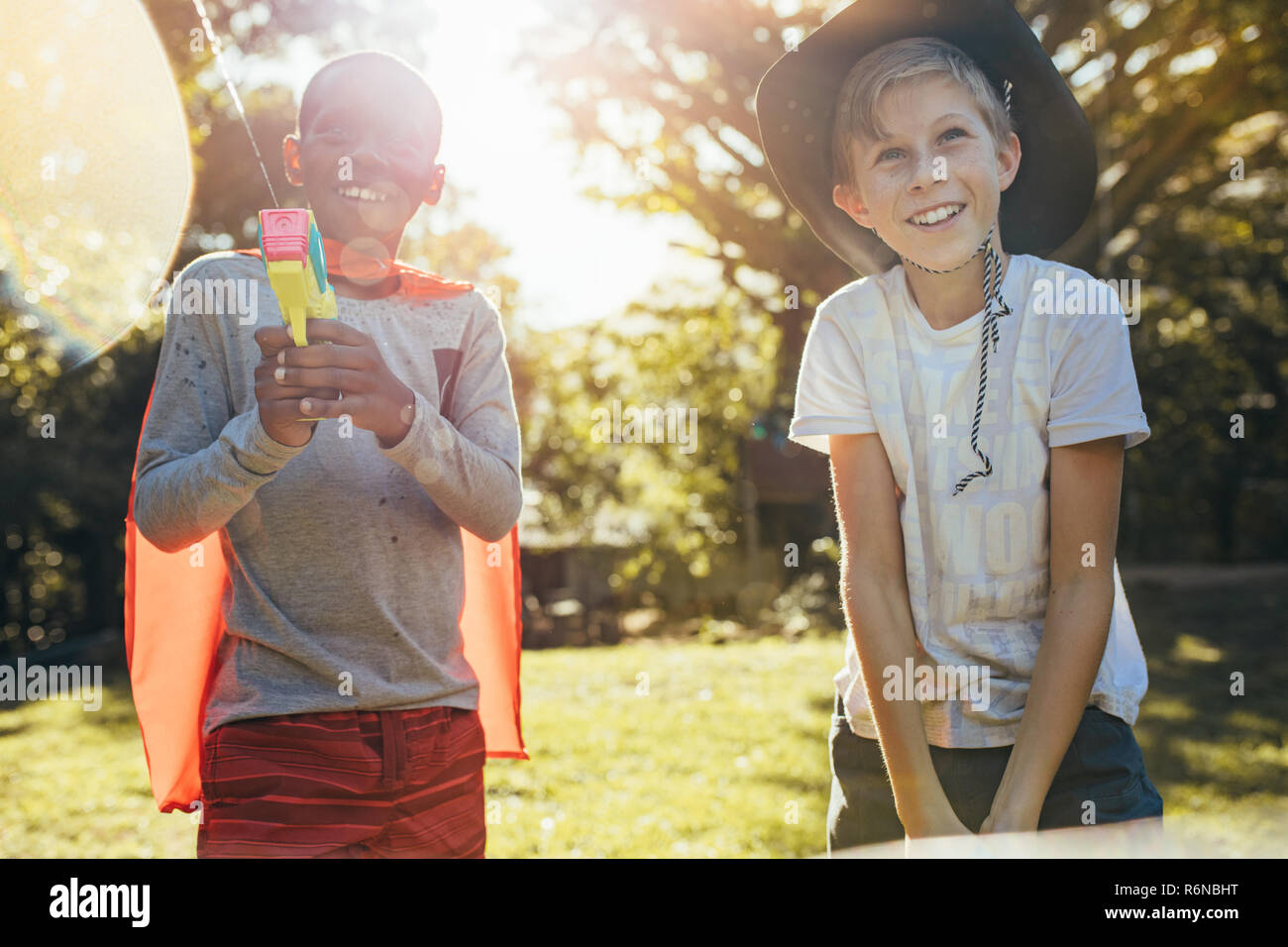 Happy young boys playing with water guns in backyard. Little boys with cape and cowboy hat playing outdoors. - Stock Image