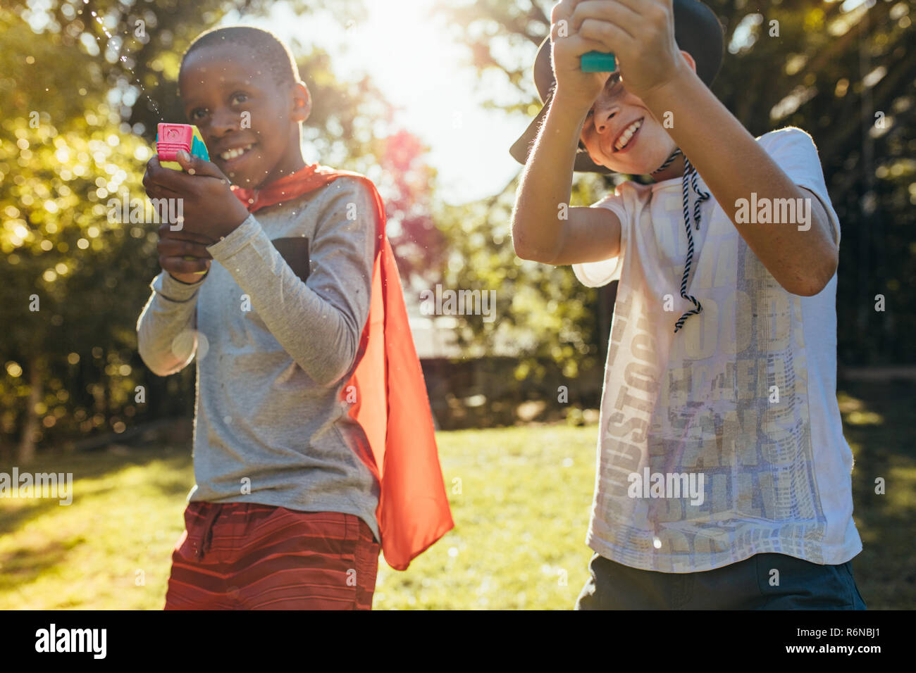 Kids playing with water guns outdoors. Little boys spraying water from a gun in backyard. - Stock Image