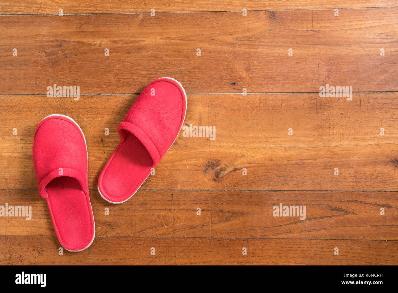 81d8b2ddb3b a pair of red slippers on the wooden floor Stock Photo  227893781 ...