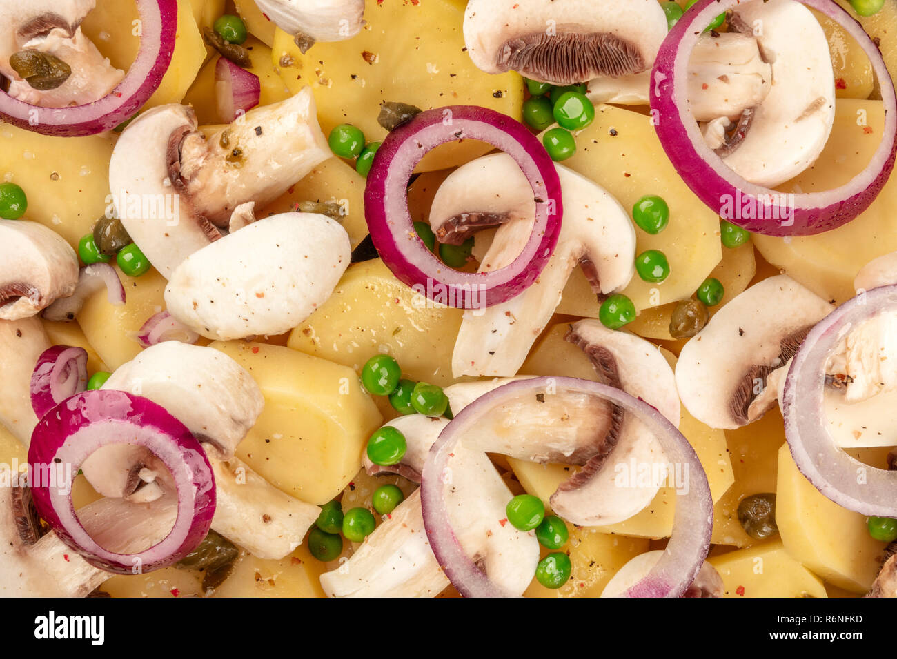 An overhead closeup photo of raw vegetables, potatoes, onions, green peas, and mushrooms, cooking a vegan dinner - Stock Image