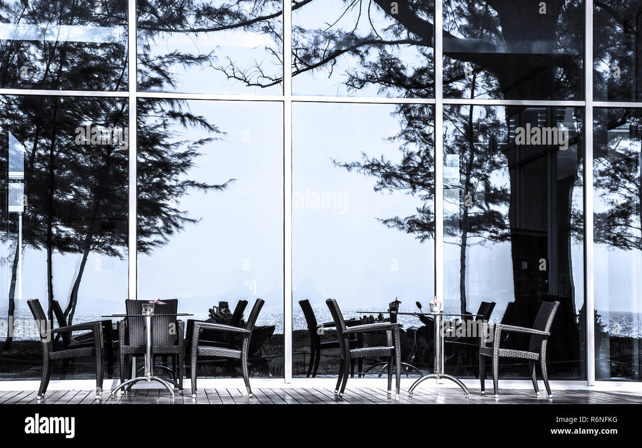 Tables and chairs in front of glass facade Nai Yang Beach, Island Phuket, Thailand. - Stock Image