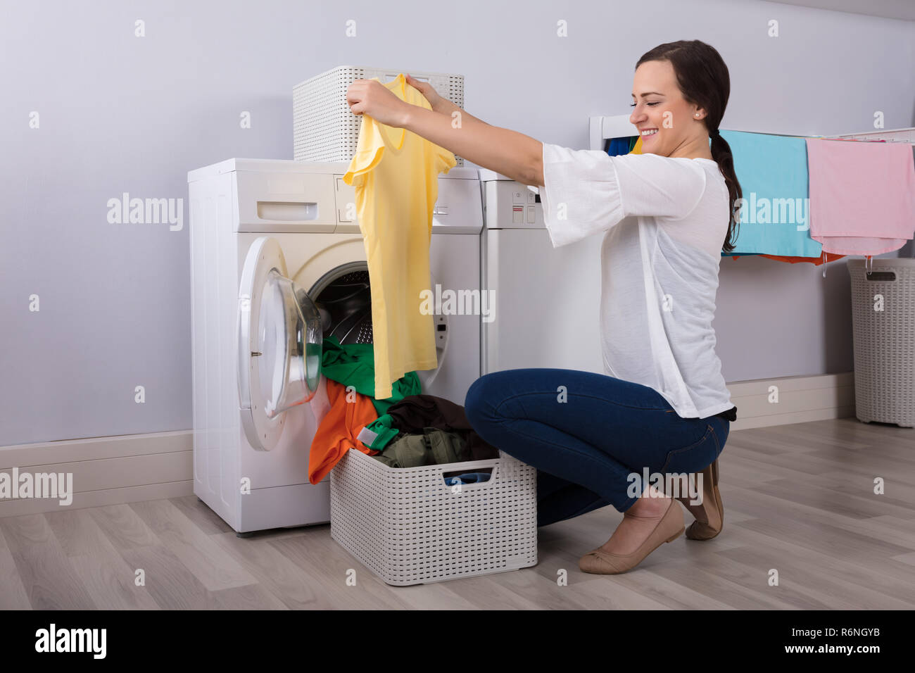 Woman Looking At Cleaned Yellow Tshirt In Laundry Room Stock Photo