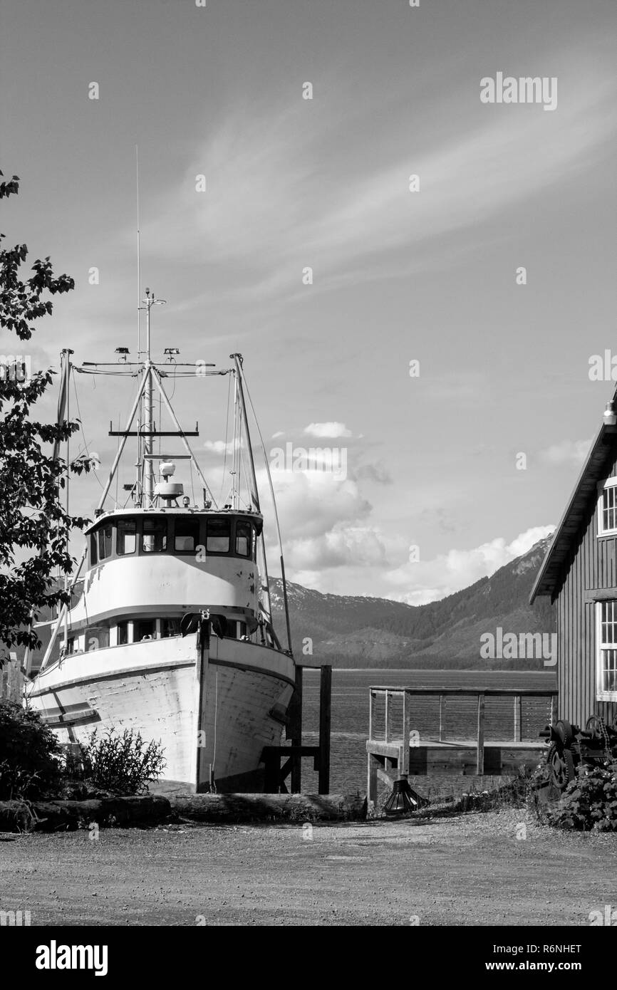 fishing boat mountain fjord wooden house cottage norwegian black white - Stock Image