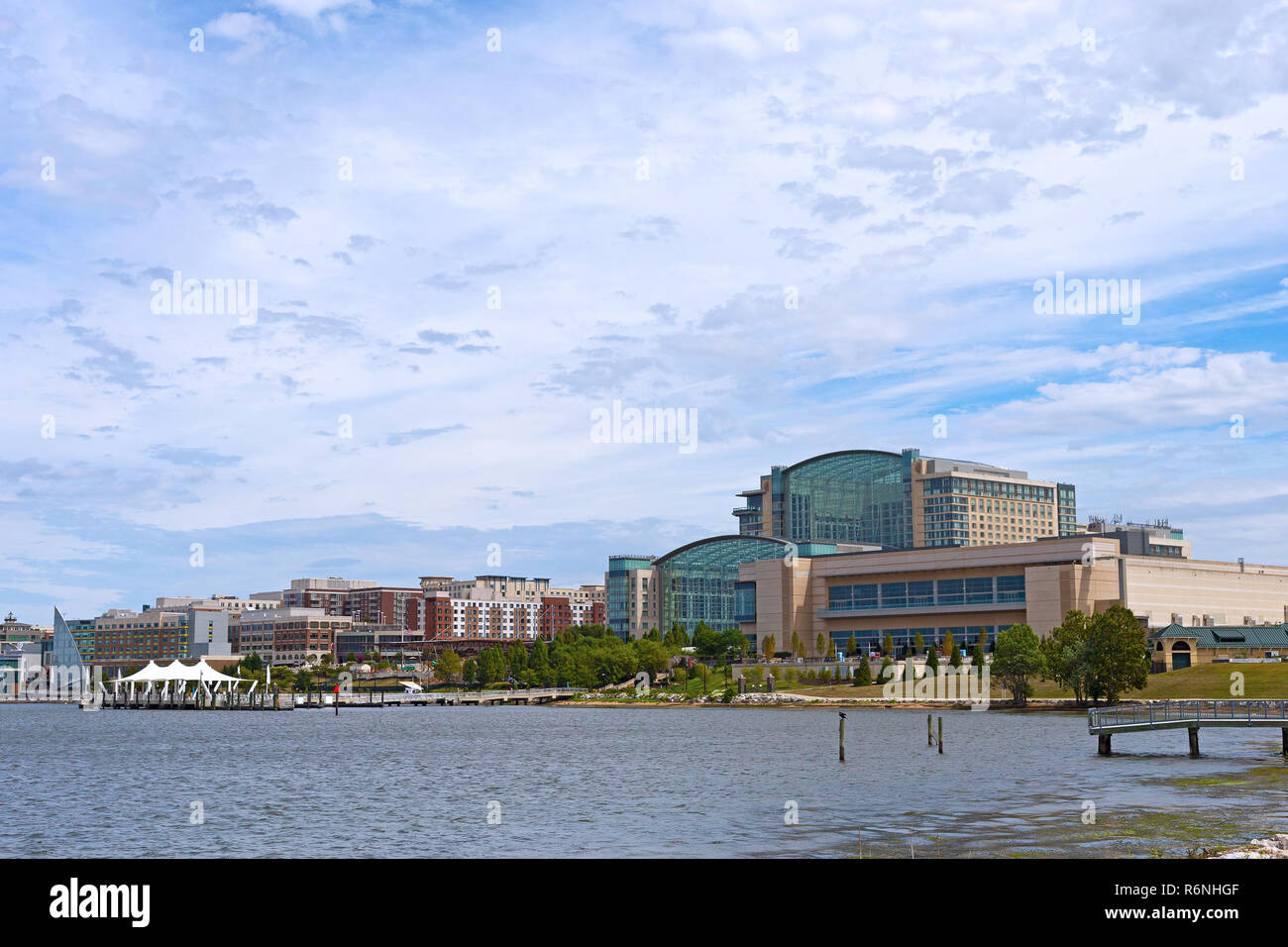 National Harbor waterfront panorama in Oxon Hill, Maryland, USA. Sun shines through cumulus clouds on National Harbor pier and modern buildings along  - Stock Image