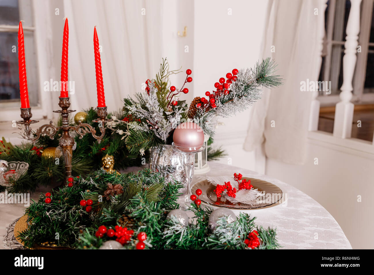 Christmas Family Dinner Table Concept Table Setting For New Year Dinner Decorations Candles And Lanterns White Tablecloth Living Room Decorated With Lights And Christmas Tree Holiday Setting Christmas Red Candles Stock Photo Alamy