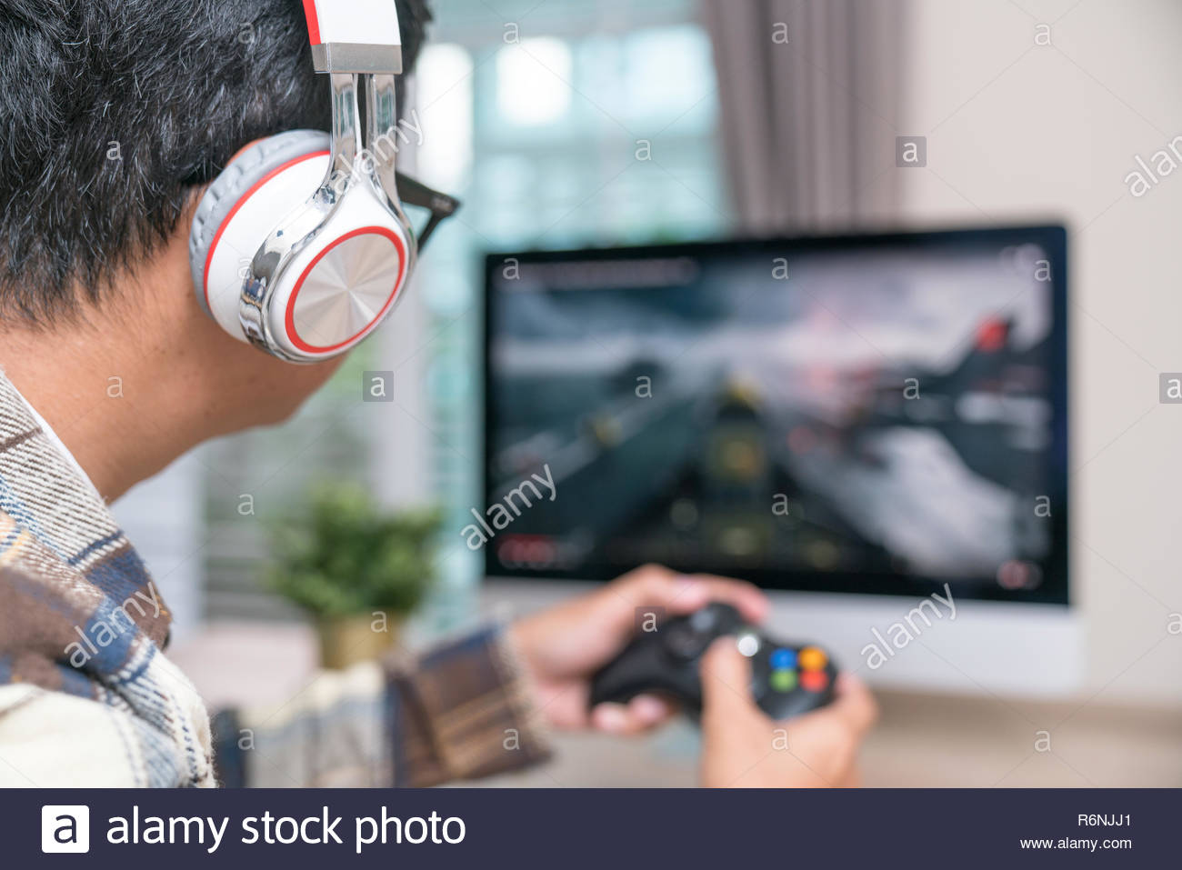 Back view of young gamer playing FPS video games at home - Stock Image