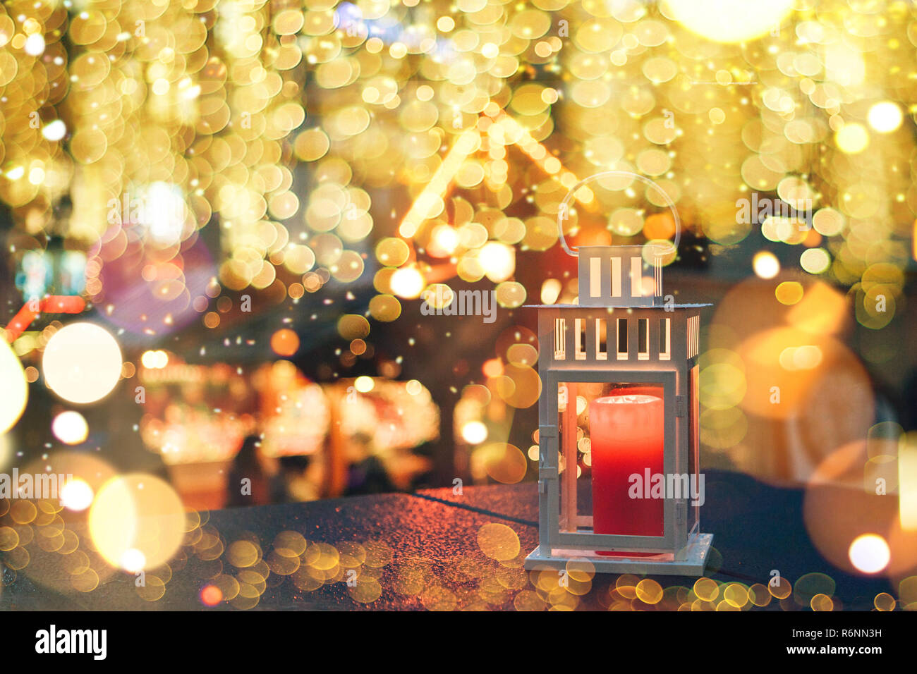 A lamp with a candle at night is decorated with Christmas lights in the background. Festive background. - Stock Image