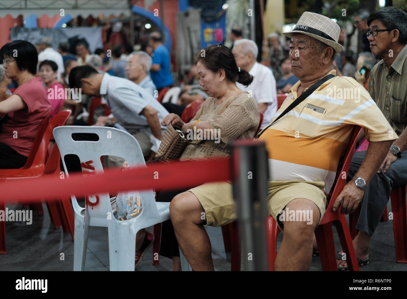 Senior Singapore citizens, ethic Chinese, watching a traditional Chinese program in an open-air venue at Telok Ayer Square, Chinatown Singapore - Stock Image