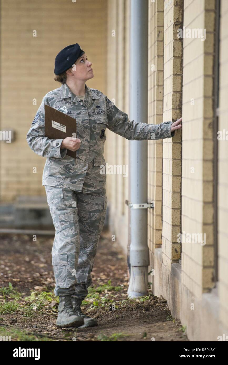 Technical Sgt. Michelle Aberle, 802nd Security Forces Squadron installation security, inspects windows during her building security check May 9, 2017, at Joint Base San Antonio-Lackland, Texas.  Aberle provides force protection for base personnel, equipment and facilities from threats to include intrusion by unauthorized people. - Stock Image