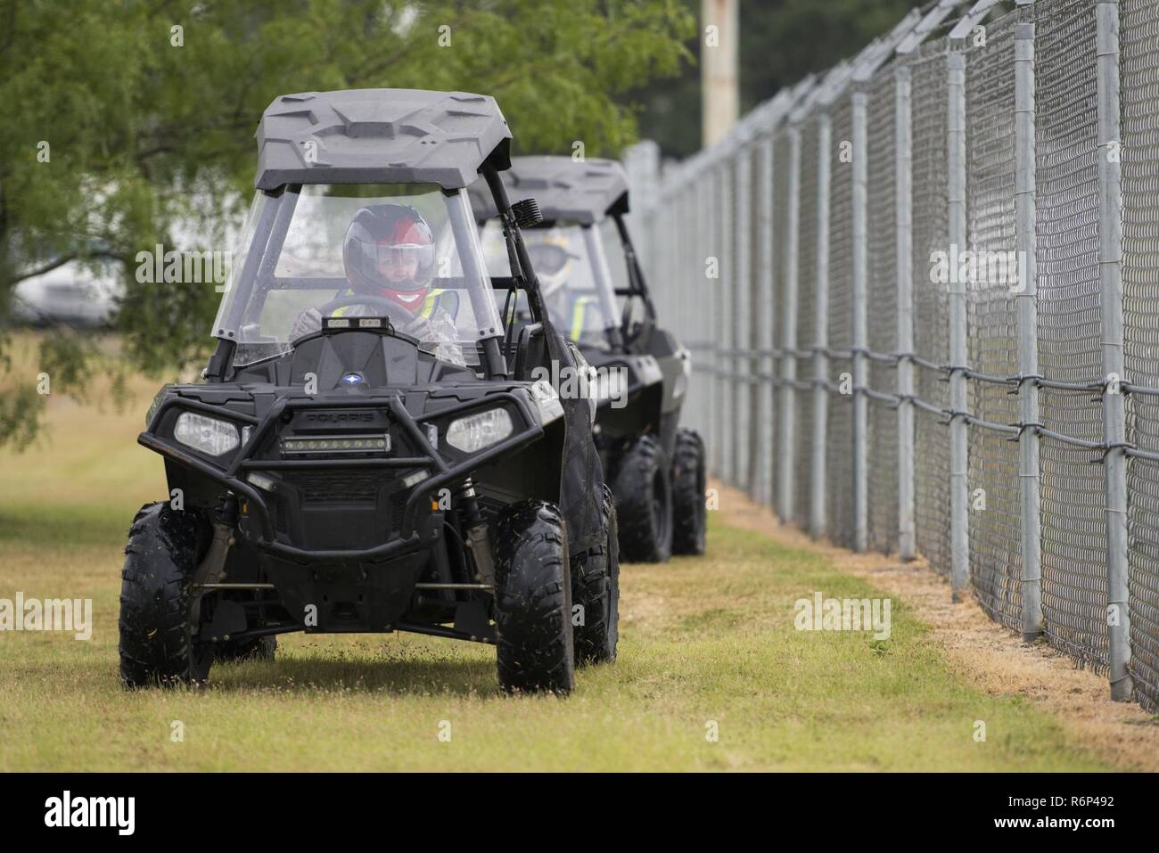 Technical Sgt. Michelle Aberle, 802nd Security Forces Squadron installation security, and Technical Sgt. Paul Turner, 802nd Security Forces Squadron installation security, drive along the base fence line during a security check May 9, 2017, at Joint Base San Antonio-Lackland, Texas.  Aberle and Turner provide force protection for base personnel, equipment and facilities from threats to include intrusion by unauthorized people. - Stock Image