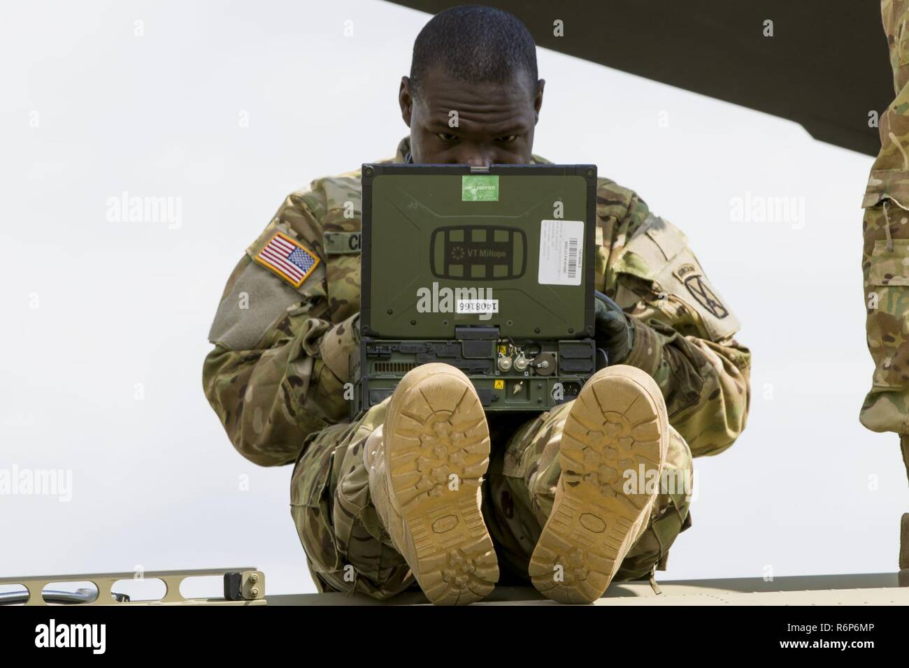 A Soldier from D Company, 3-10 General Support Aviation Battalion, refers to repair procedures during the replacement of the aft yoke in a CH-47 Chinook helicopter at Lielvarde, Latvia, on May 19. The highest ranking member of the team was a specialist; empowering junior leaders is imperative to be successful in the spread-out environment of U.S. Army Europe's Atlantic Resolve mission. - Stock Image