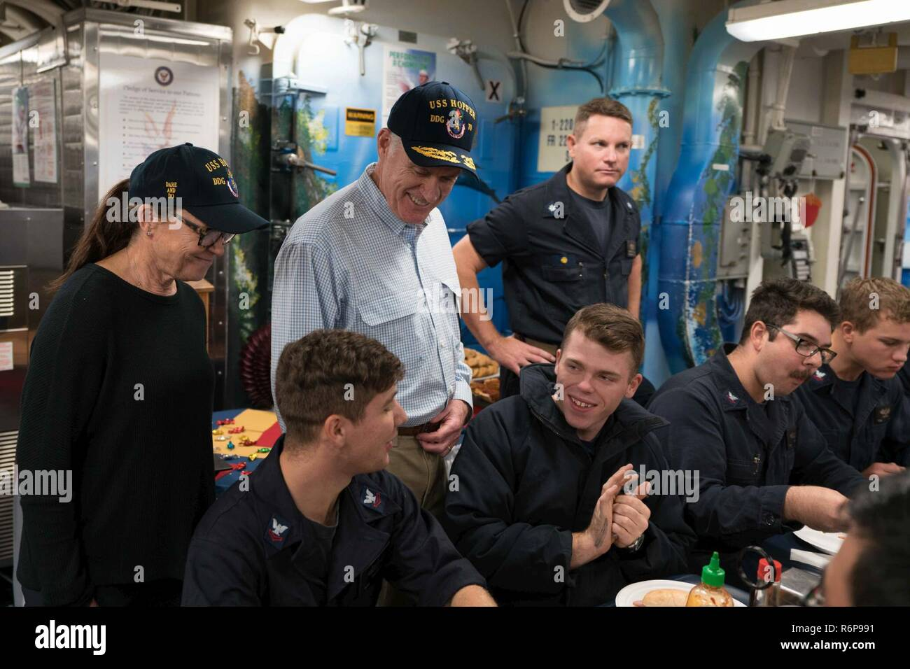 ARABIAN GULF (Nov. 23, 2017) Secretary of the Navy (SECNAV) Richard V. Spencer (center), and his wife, Sarah Pauline Spencer, meet with crewmembers of the Arleigh Burke-class guided-missile destroyer USS Hopper (DDG 70) on the ship's mess decks during the SECNAV's visit to the ship on Thanksgiving Day. Hopper is deployed to the U.S. 5th Fleet area of operations in support of maritime security operations to reassure allies and partners and preserve the freedom of navigation and the free flow of commerce in the region. - Stock Image