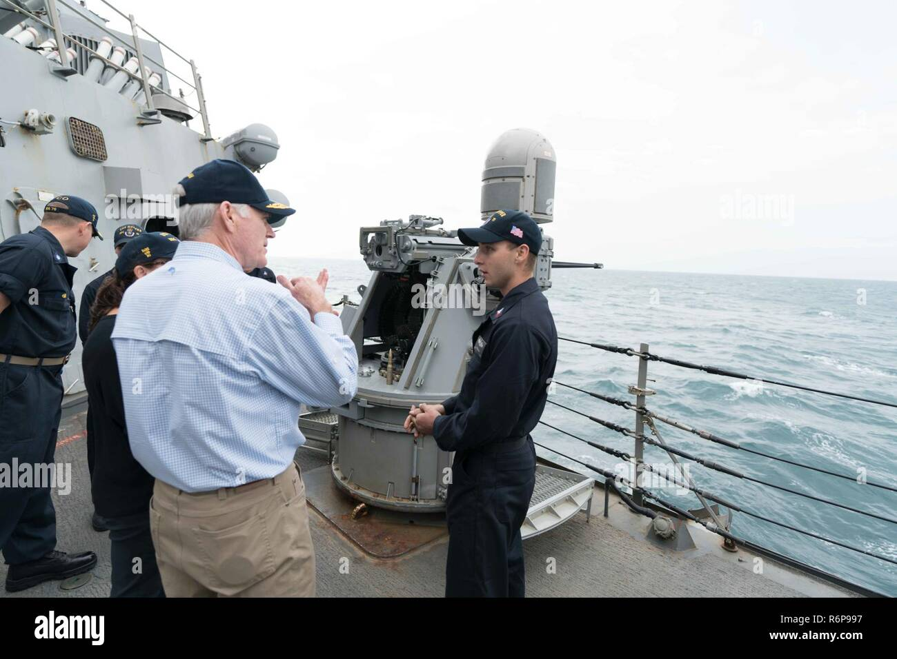 ARABIAN GULF (Nov. 23, 2017) Secretary of the Navy Richard V. Spencer speaks to Gunner's Mate 1st Class Benjamin Schreiner, assigned to the Arleigh Burke-class guided-missile destroyer USS Hopper (DDG 70), during a tour of the ship on Thanksgiving Day. Hopper is deployed to the U.S. 5th Fleet area of operations in support of maritime security operations to reassure allies and partners and preserve the freedom of navigation and the free flow of commerce in the region. - Stock Image