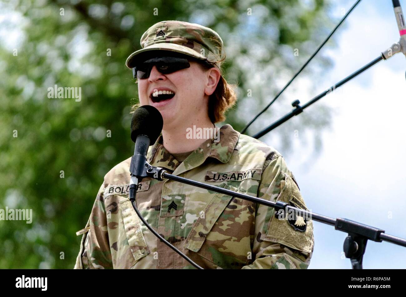 Sgt. Katherine Bolcar, 101st Airborne Division Band and vocalist for Big 5, serenades the crowd gathered at the Air Assault School's community fair for Week of the Eagles. - Stock Image