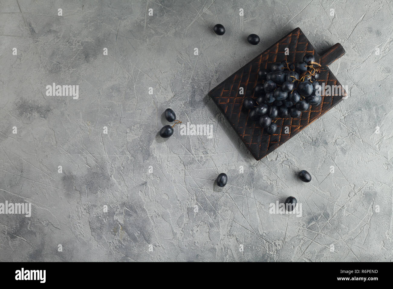 Dark grapes on the board on a textured gray background. Top view with space for text. Stock Photo