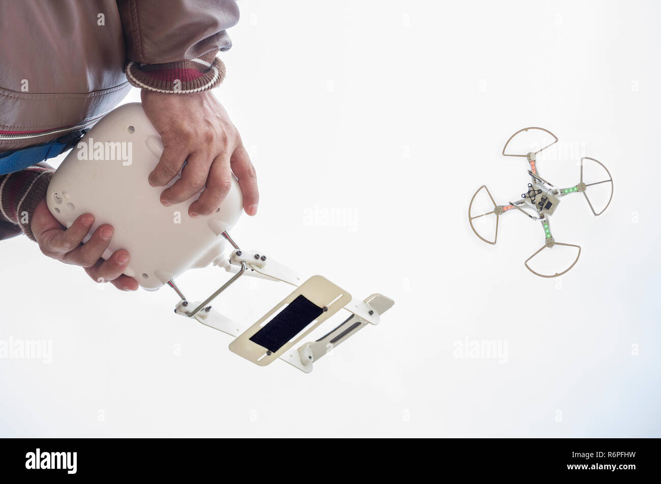 Pilot flying drone with FPV mount empty on remote controller - Stock Image