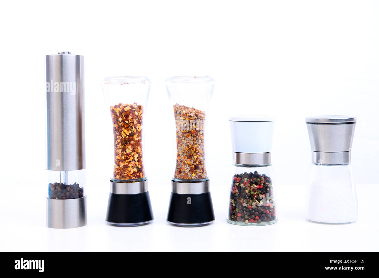 different spice mills with salt,pepper and other herbs - Stock Image