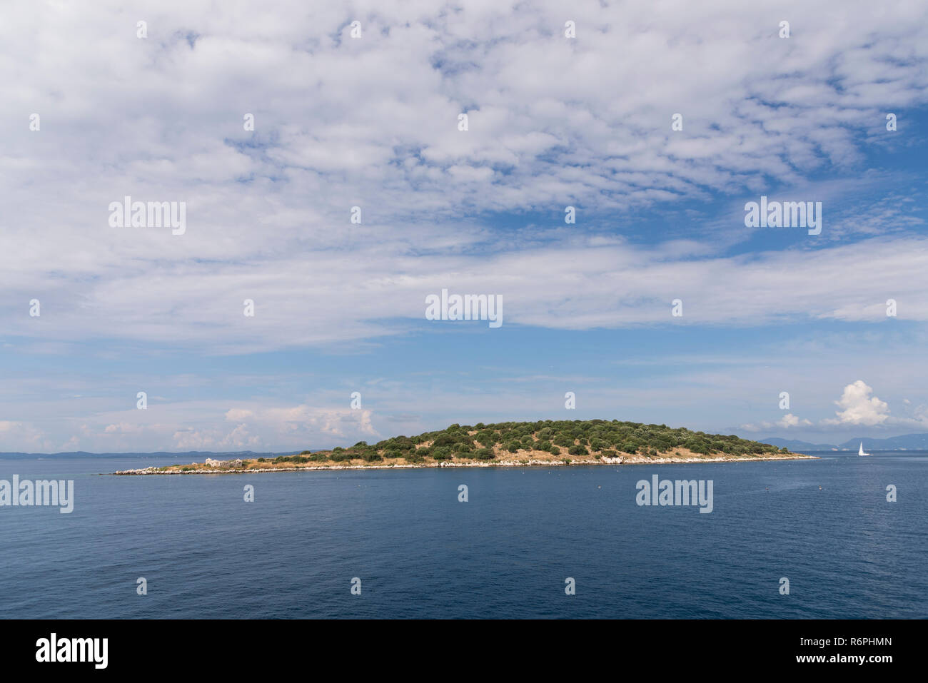 Island and sailboat in the ionian sea with a cloudy sky. - Stock Image