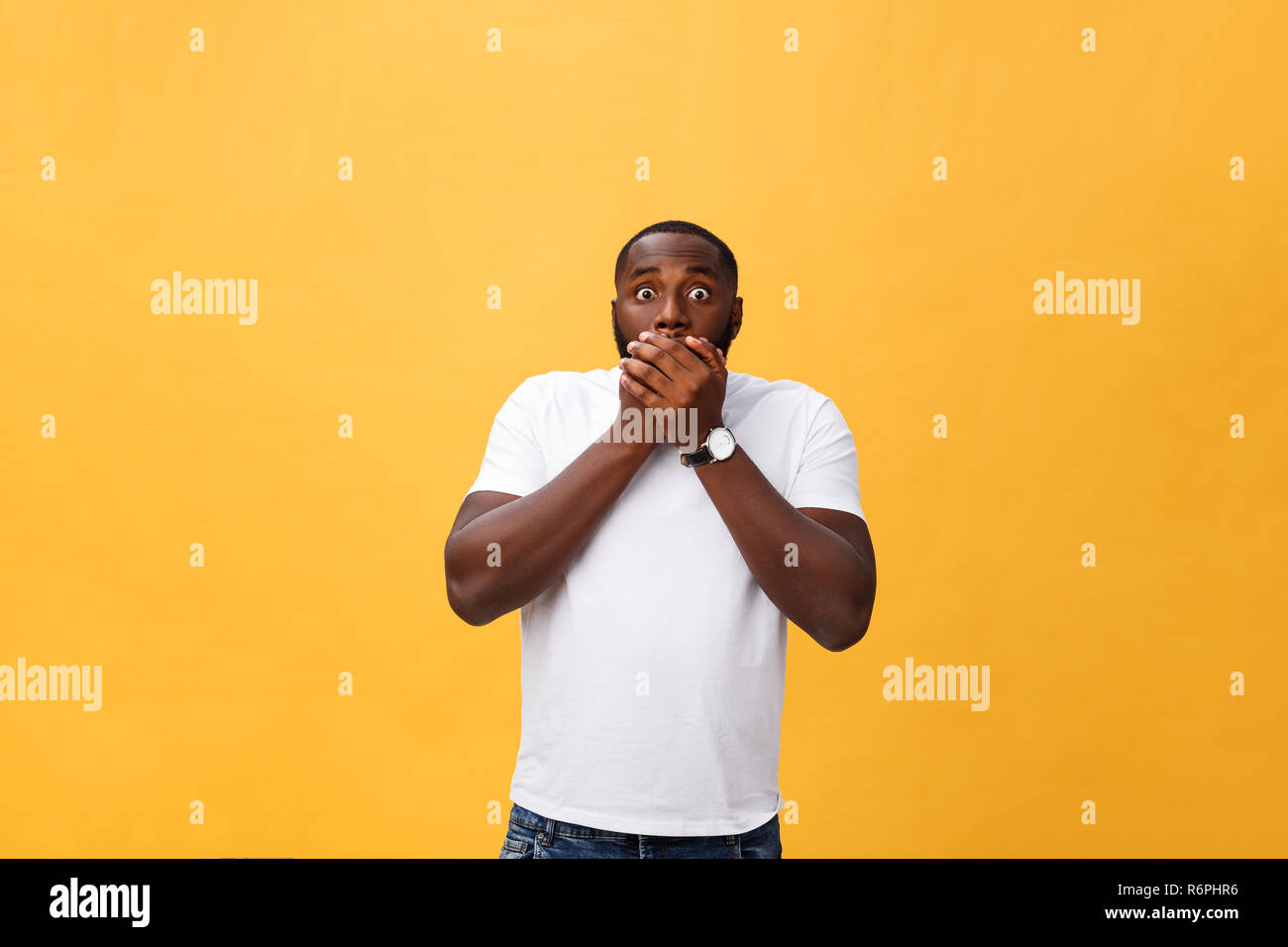 Amazed young African American hipster wearing white t-shirt holding hands in surprised gesture, keeping mouth wide open, looking shocked - Stock Image