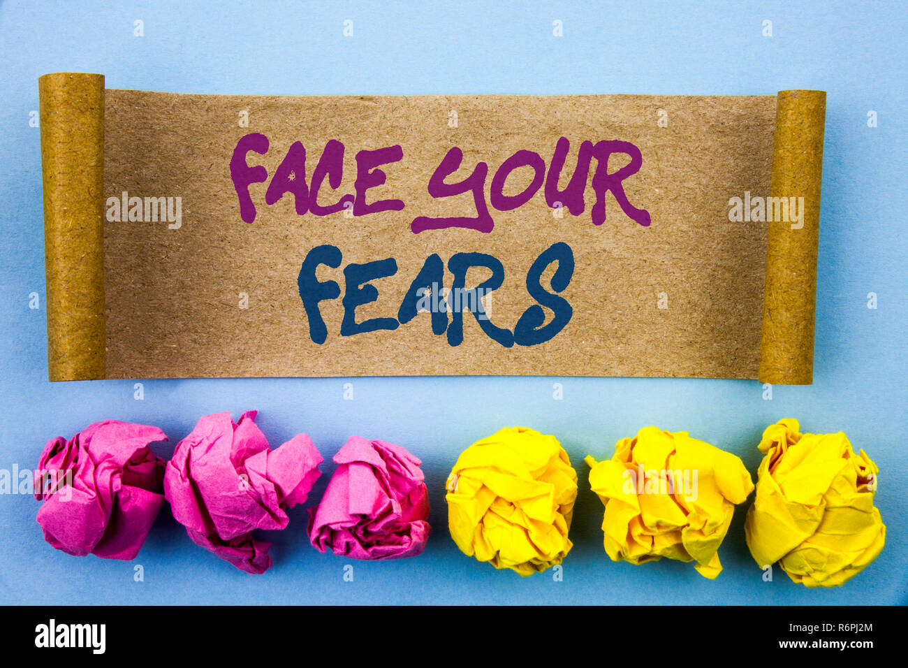 Handwriting text showing Face Your Fears. Concept meaning Challenge Fear Fourage Confidence Brave Bravery written on tear sticky note Paper on the blue background Folded paper Stock Photo