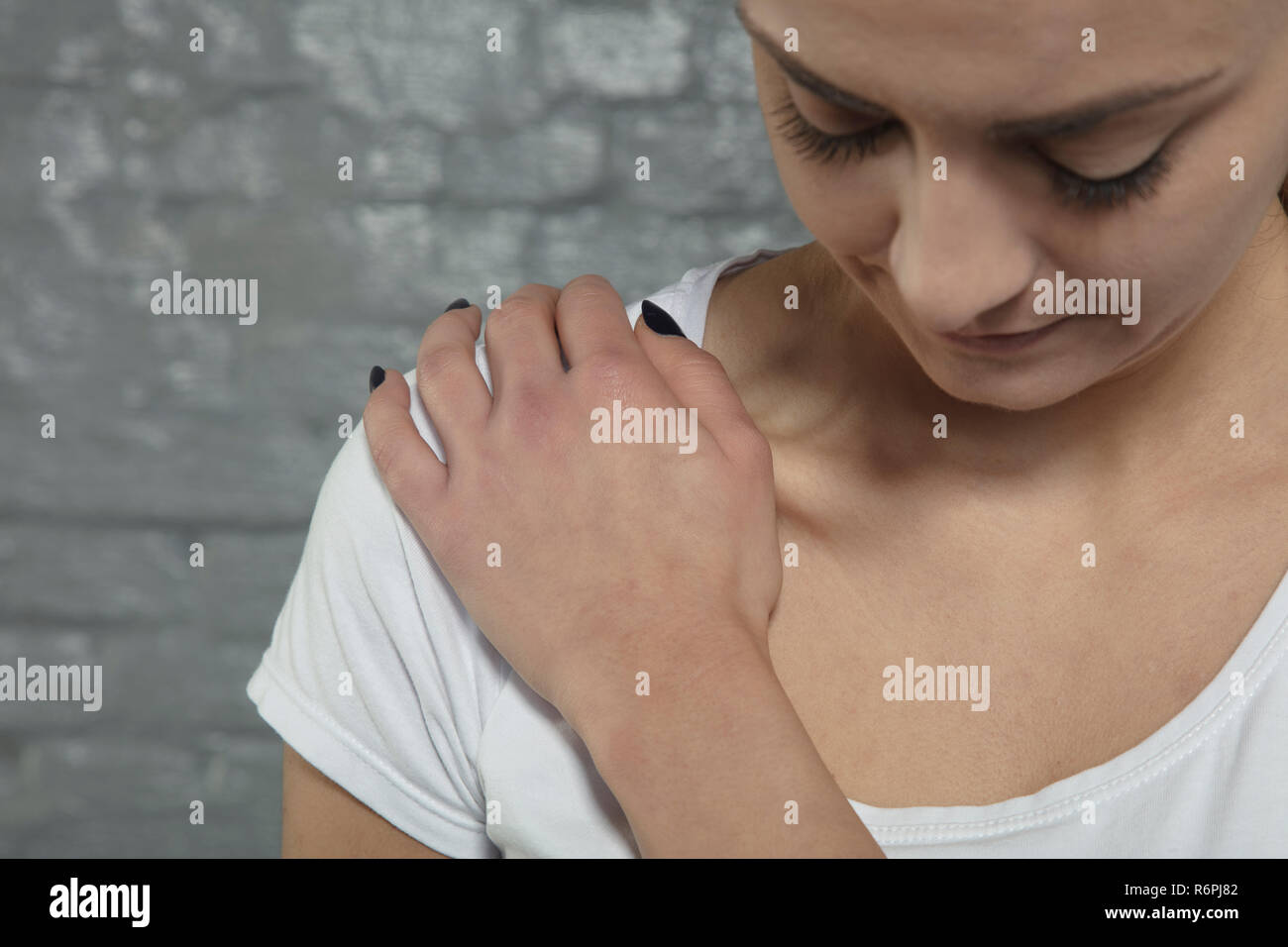 woman is struggling with shoulder pain, close up - Stock Image