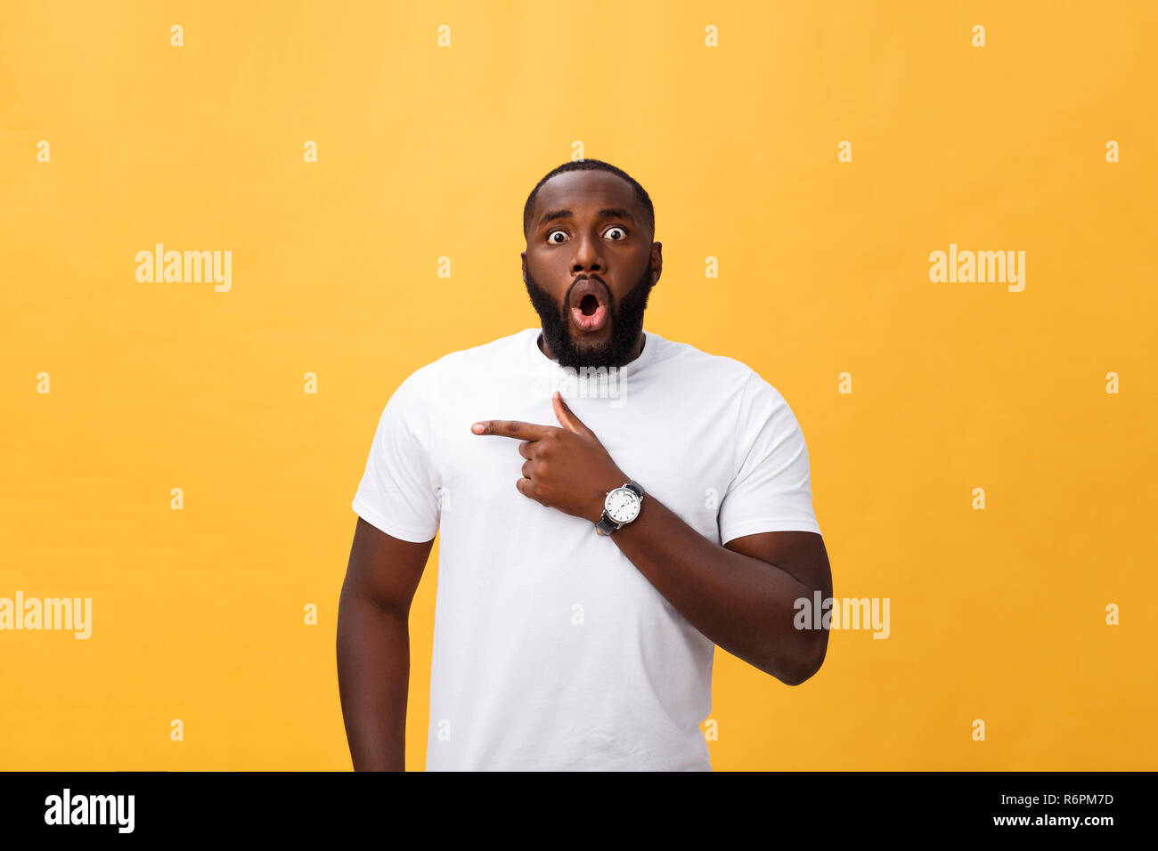 Amazed young African American hipster wearing white t-shirt holding hands in surprised gesture, keeping mouth wide open, looking shocked. - Stock Image