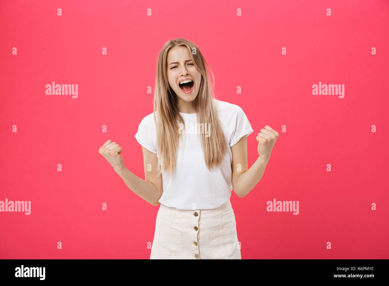 Young woman getting angry ,crazy and shouting isolated on a pink background. - Stock Image