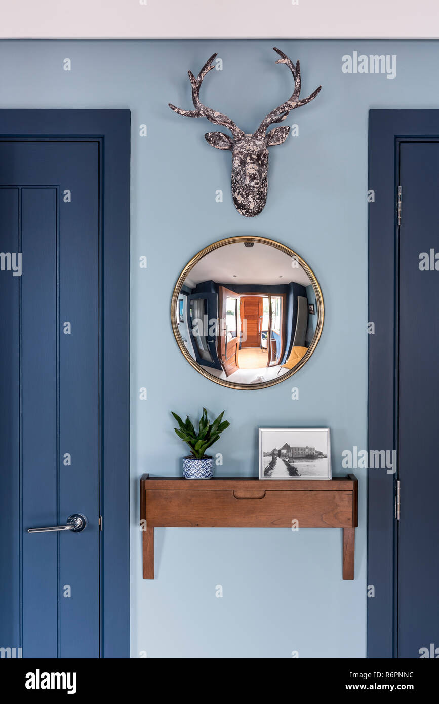 Wall mounted cherrywood drawer unit and convex mirror in Hampshire Mill house redesigned by Emma Painter - Stock Image