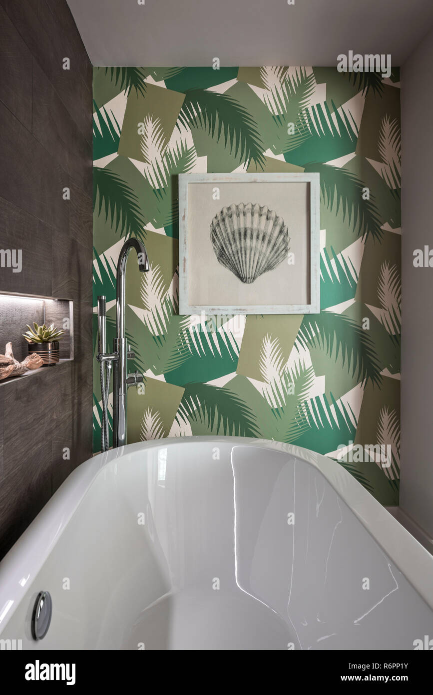 Deco Palm Green wallpaper by Cole & Son with freestanding bath in Hampshire Mill house redesigned by Emma Painter - Stock Image