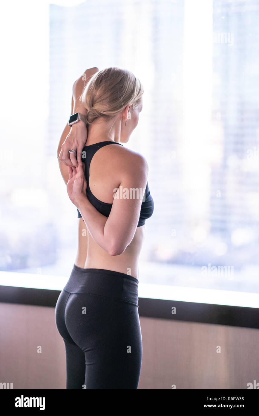 Traveling woman in city metro hotel room doing yoga and stretching exercises - Stock Image