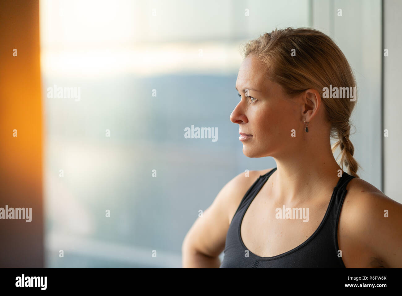 Young cute woman inspired to be healthy -- thinking about wellness in exercise clothes - Stock Image