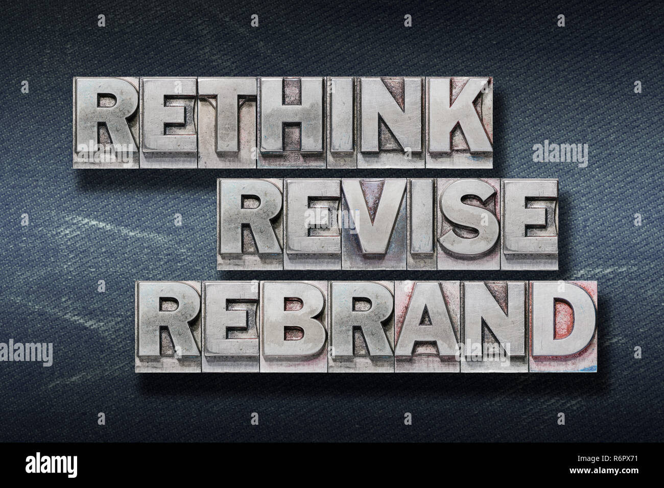 rethink revise rebrand words made from metallic letterpress on dark jeans background - Stock Image