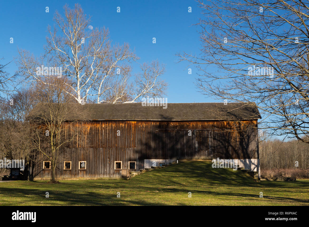 The moon rising above an old barn on the Stanford House property. Cuyahoga Valley National Park, Ohio - Stock Image