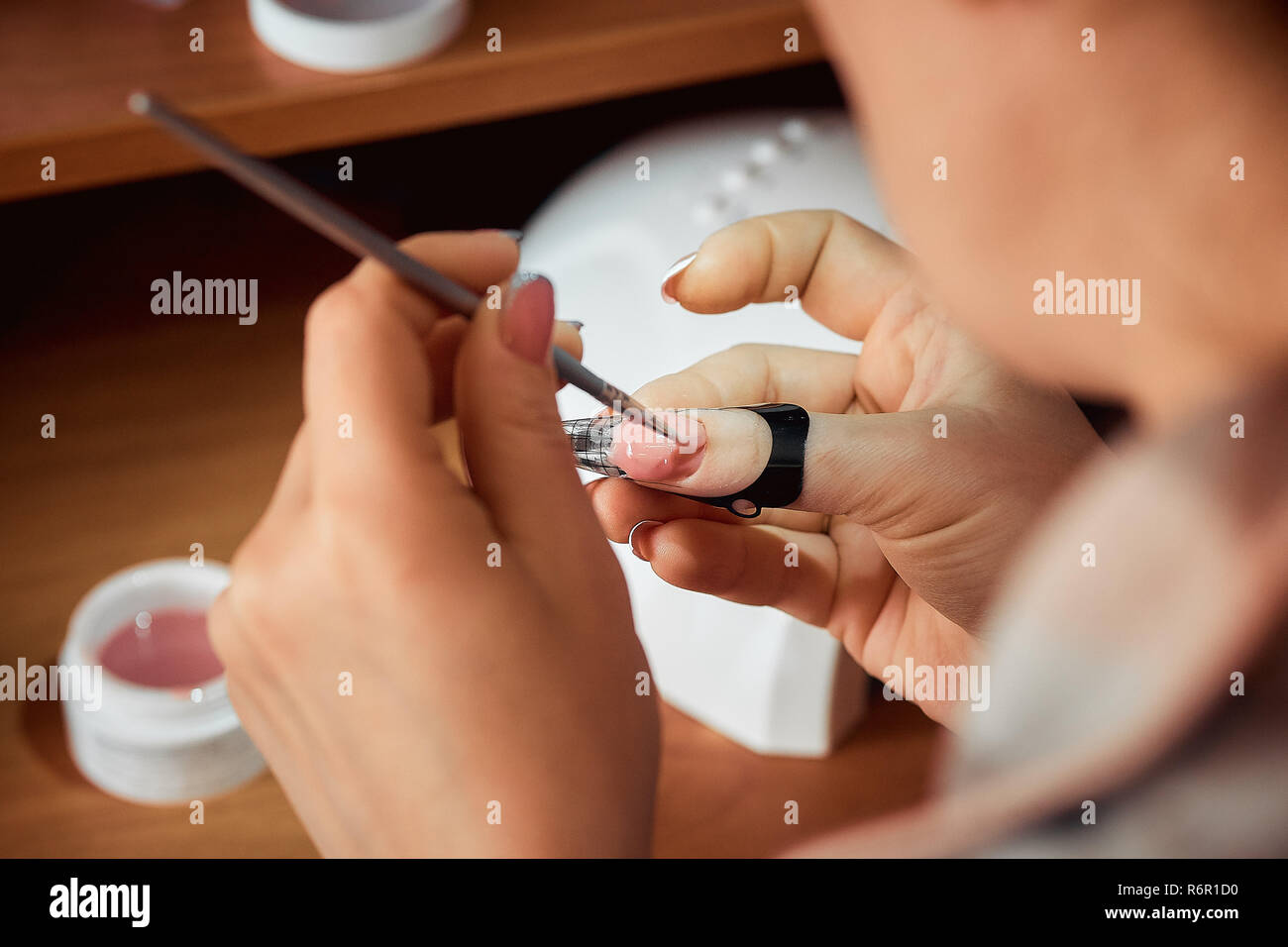 applying gel nail Polish, the woman doing the manicure Stock Photo ...