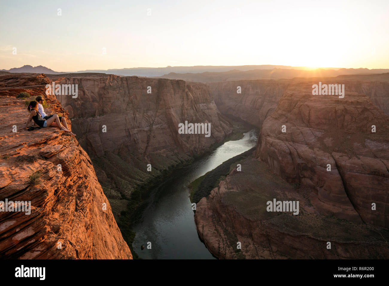 Zwei Touristen schauen sich den Sonnenuntergang an, Horseshoe Bend, Colorado River, Page, Arizona, USA - Stock Image