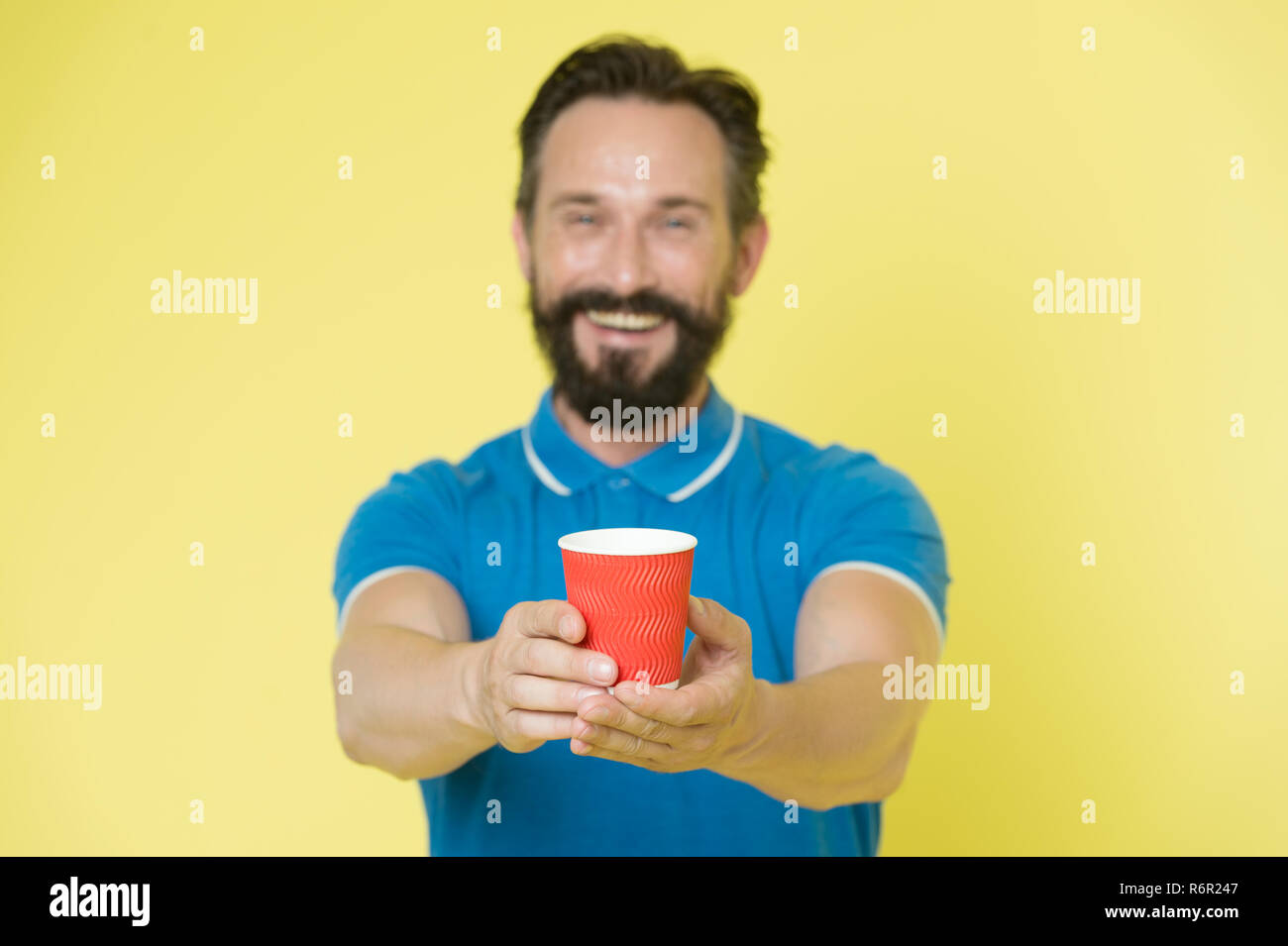 Guy beard and mustache holds paper cup of tea or coffee. Offer drink to you. Trainer experienced man care about water balance. Share and generosity concept. Have a sip. Take this if you want to drink. - Stock Image