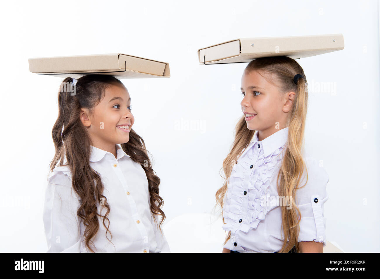 Find balance. Schoolgirls with cute pony tails hairstyle carry folders on heads. Perfect schoolgirls with tidy fancy hair and proper posture carry folders on heads. Balance and burden of knowledge. - Stock Image