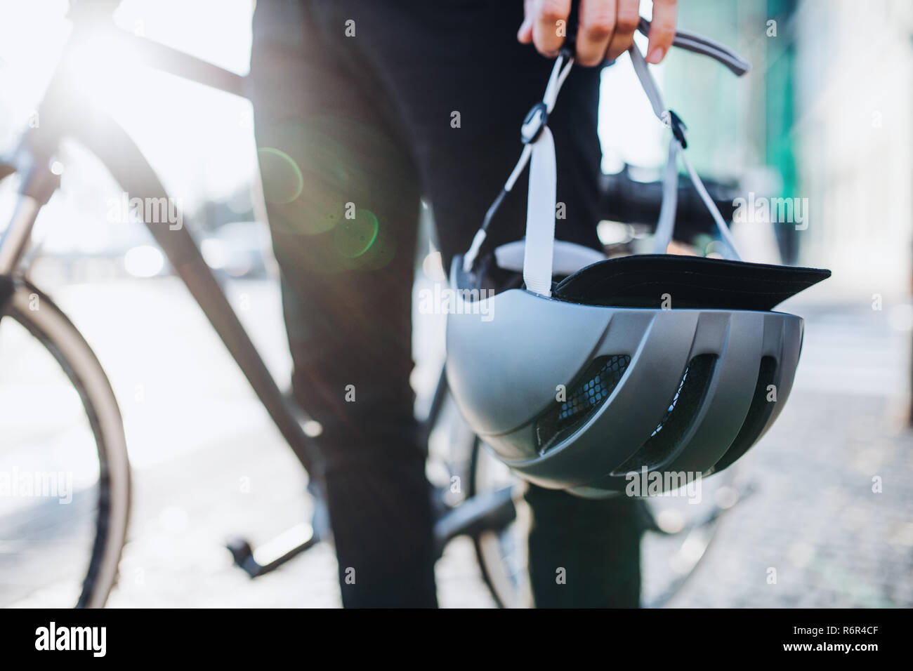 Midsection of man commuter or courier with electric bicycle in city, holding helmet. Stock Photo