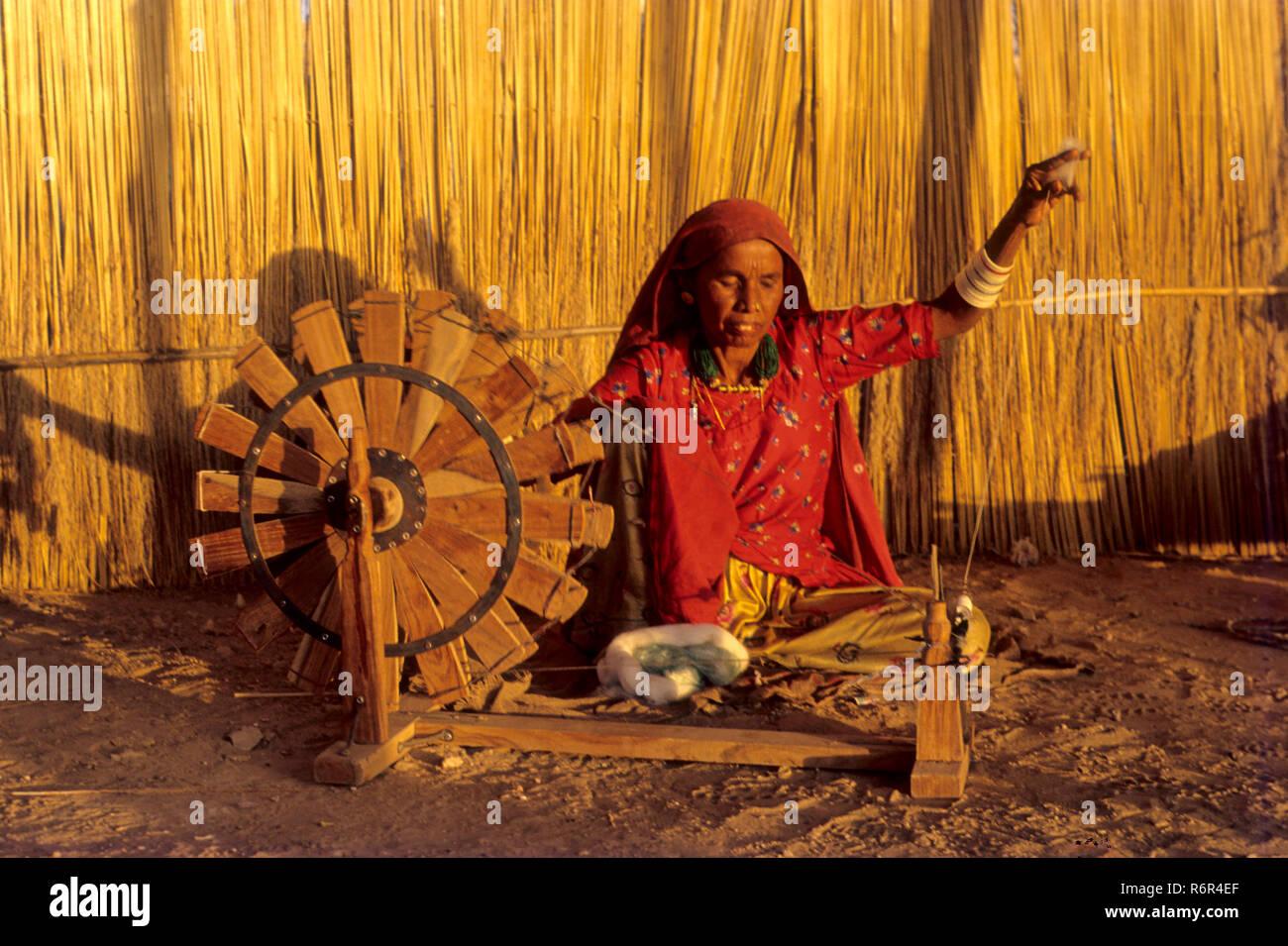 woman working spinning wheel charkha, handloom weaving