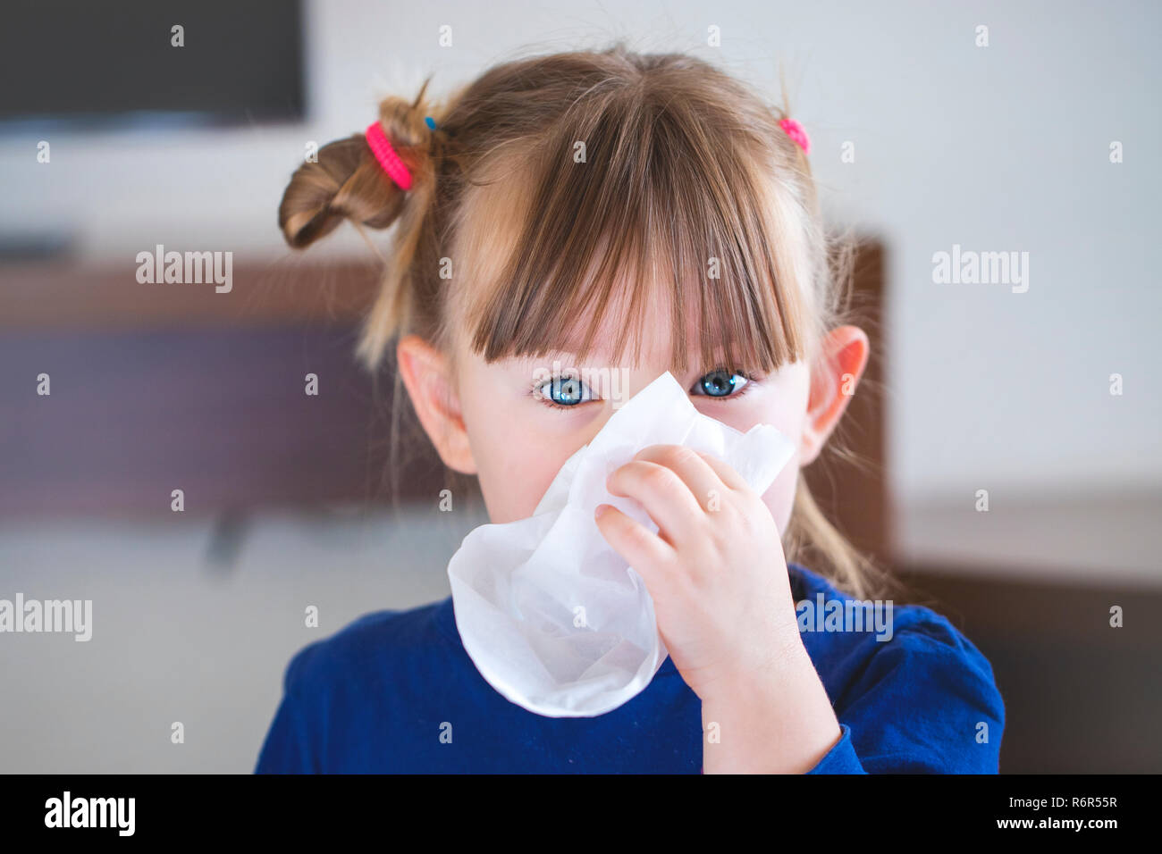 little girl blowing her nose into a handkerchief. - Stock Image