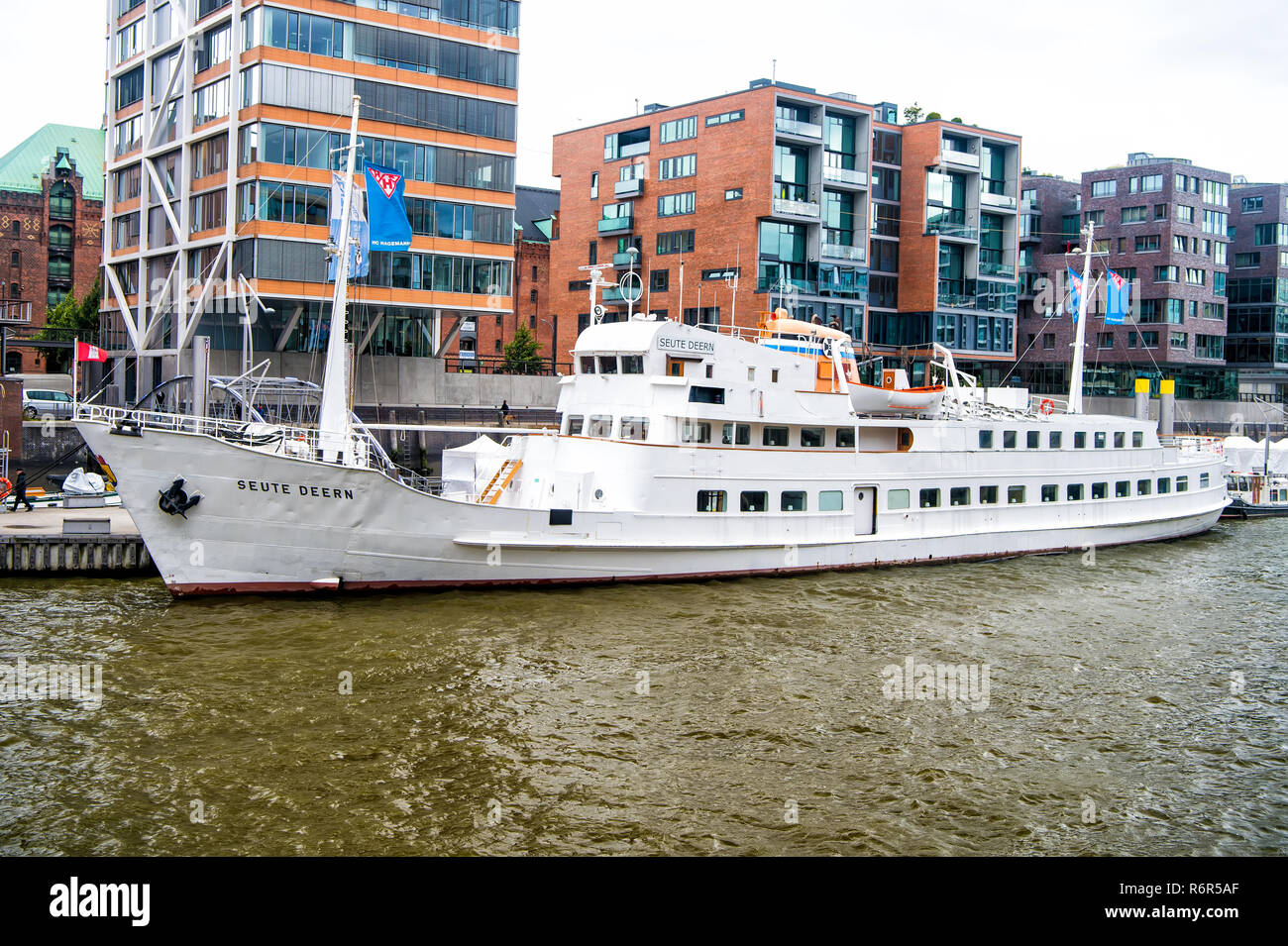 Hamburg, Germany - September 07, 2017: ship at ferry pier on cityscape background. River transport, transportation. Water travel, travelling, trip. Vacation, discovery, wanderlust. Stock Photo