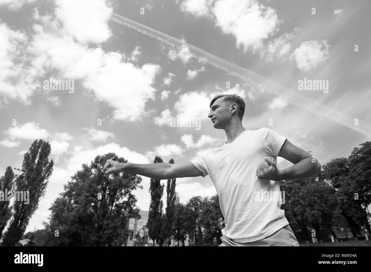 workout of man punching sunny outdoor on blue sky, sport and fitness - Stock Image