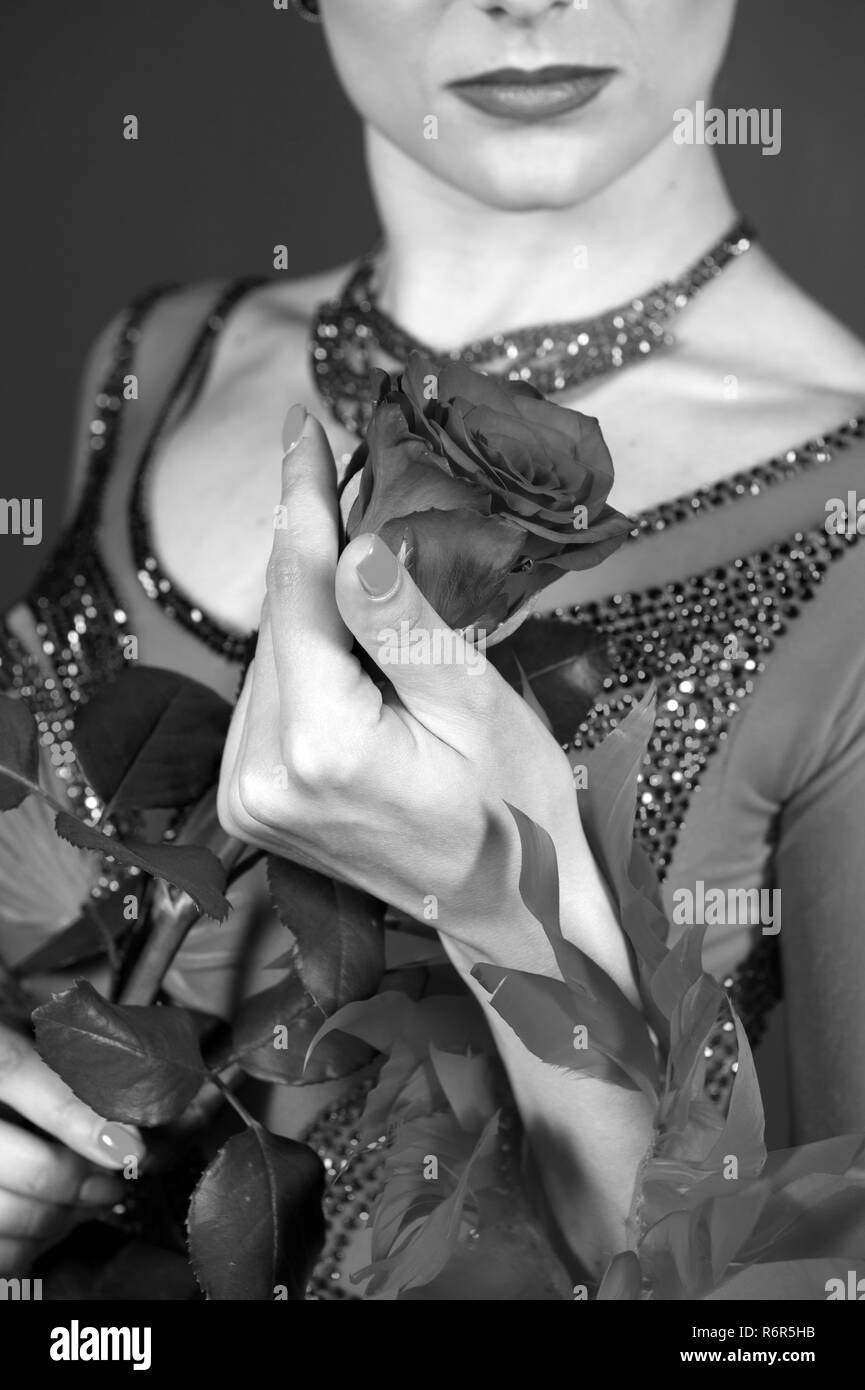 Rose flower in female hand, womens day. Love, desire, romance. Floristry, decor, design, floral shop. Womens day, 8 march, spring. Birthday, anniversary, holidays celebration, black and white - Stock Image