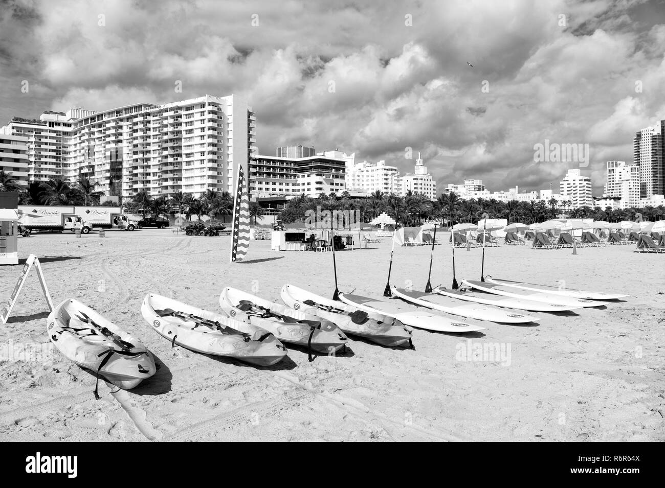 Miami, south beach. kayak and surfboards with paddles on sand, sandy beach, tropical palm resort, sunny day on city skyline clouds on blue sky. Idyllic summer vacation. Active lifestyle. Water sports - Stock Image