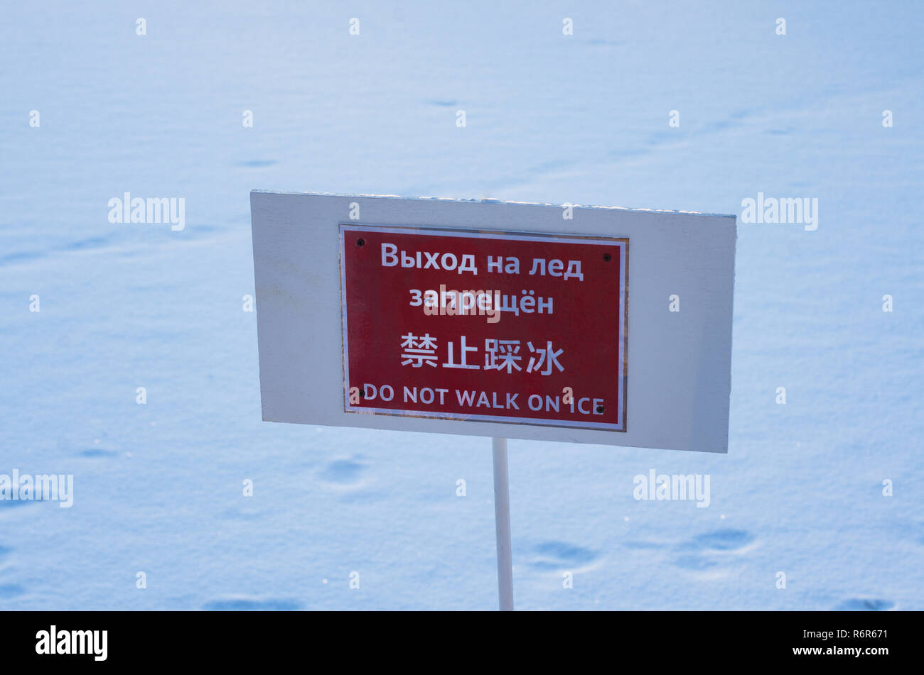 Warning information plate with the inscription 'do not walk on ice' in Russian, Chinese and English Stock Photo