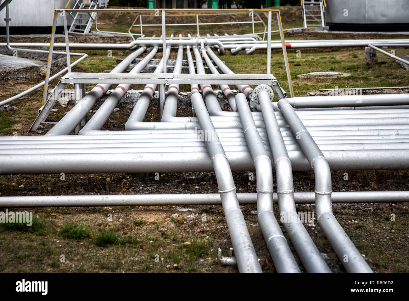 pipes and valves at oil refinery - Stock Image