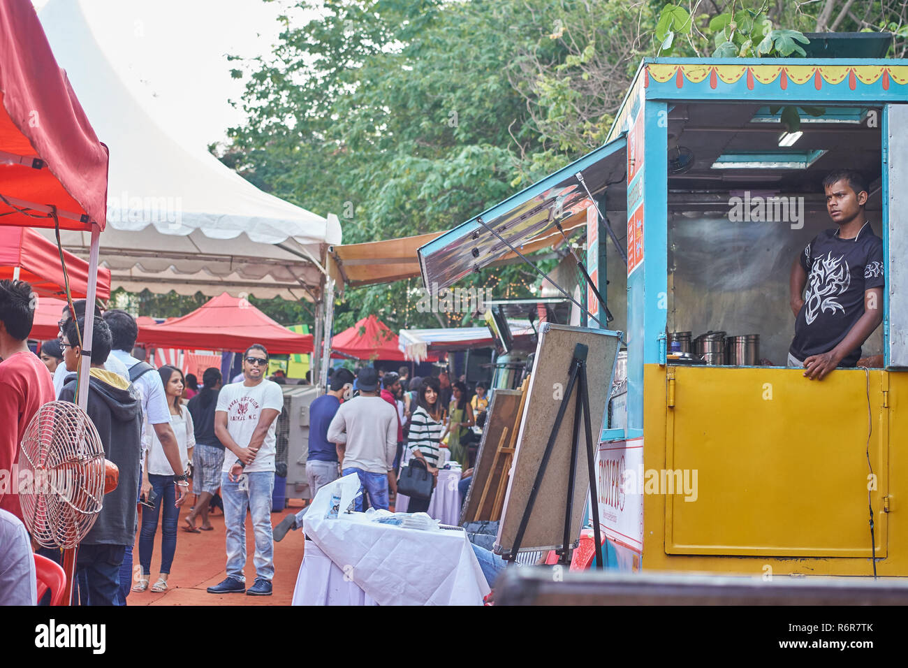 Man relaxing in his food truck at a food festival in Bangalore. - Stock Image