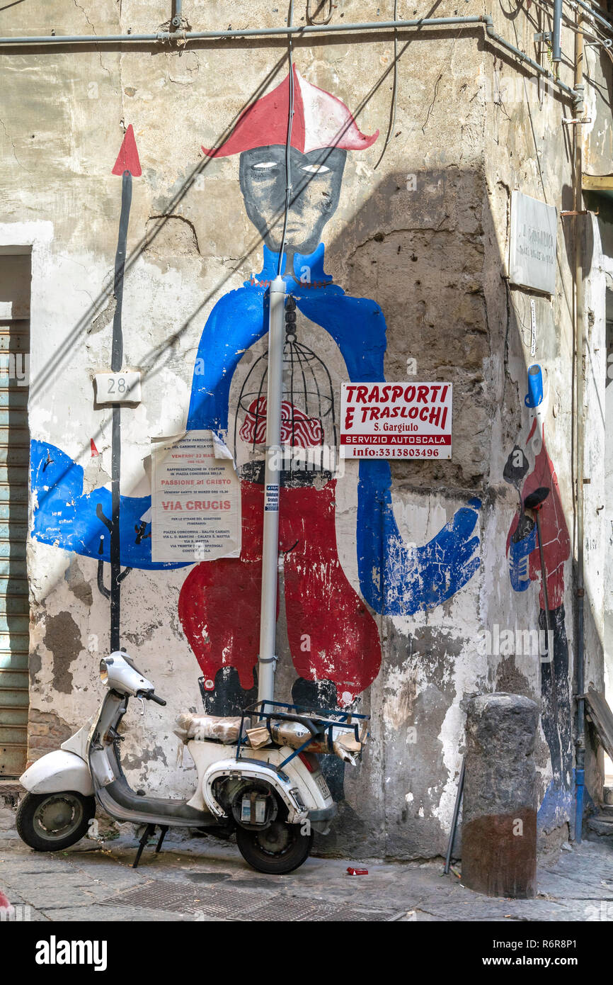 An old scooter parked by a wall frescoe of Pulcinella, a popular figure in the Commedia dell'art and street theater since the 17th cen.  in the Quarti - Stock Image
