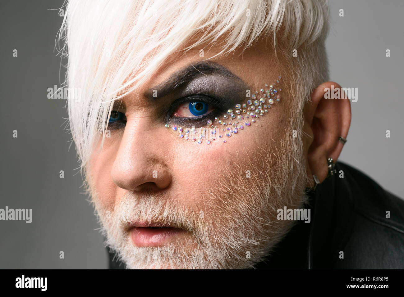 Bisexual by nature, queer by choice. Exotic hipster man with fashion hairstyle. Male makeup look. Bearded man with male makeup. Transgender person.Hipster fashion style. Support transgender rights - Stock Image