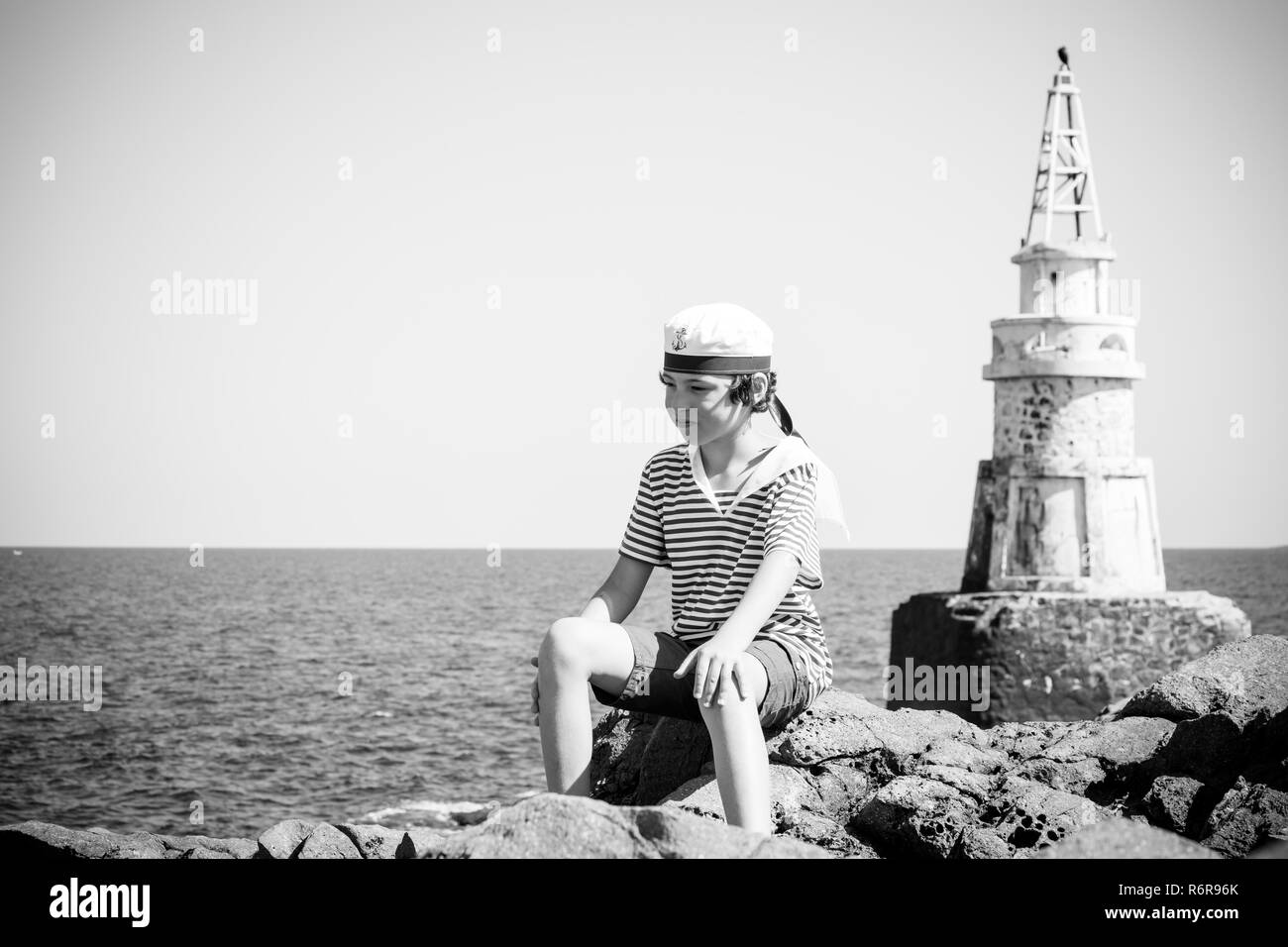 A boy in a striped T-shirt and cap sits on the rocks. In the background stands a lighthouse. Black and white. Stylization, vignetting. - Stock Image